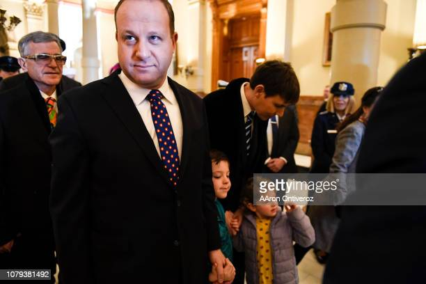 Governorelect Jared Polis stands with his partner Marlon Reis and their children Cora and Caspian in the west wing before his inauguration at the...