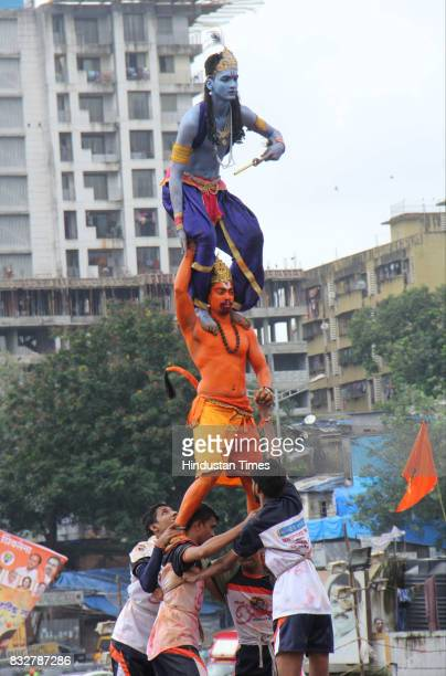 Govindas in Lord Krishna and Hanuman outfits form human pyramid to break earthen pots during Dahi Handi celebration on the occasion of Krishna...