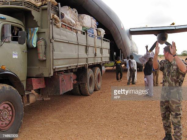 A French soldier guides a truck as it backs up against a French Airforce transport plane loaded with humanitarian aid at an airstrip just outside Goz...