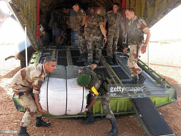A French soldier helps unload a French Airforce transport plane loaded with humanitarian aid at an airstrip just outside Goz Beida which is 90...