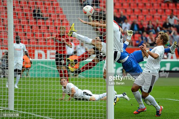 Gozalo Castro of Leverkusen scores his teams first goal against goalkeeper Oliver Baumann and Mensur Mujdza of Freiburg during the Bundesliga match...