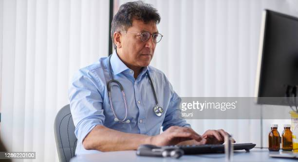 gp writing letter on computer - doctor stock pictures, royalty-free photos & images