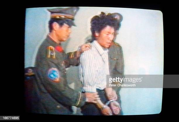"""Grab frame"""" picture from a TV screen showing Chinese State Television footage of the arrest of a Tiananmen Square protestor being taken to trial.."""