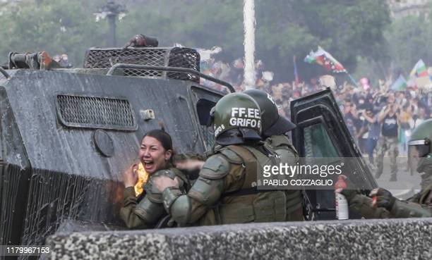 TOPSHOT Grab taken from AFP video shows a riot police officer been reached by a petrol bomb during clashes with demonstrators protesting against the...