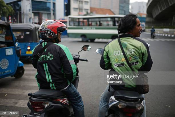 A GrabBike motorcycle driver left and a GoJek motorcycle driver wait for orders in Jakarta Indonesia on Sunday Aug 13 2017 PresidentJokoWidodois...