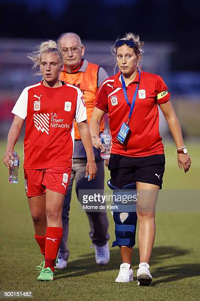 Grace Abbey of Adelaide walks with injured Adelaide player Marijana Rajcic during the round eight WLeague match between Adelaide United and Perth...