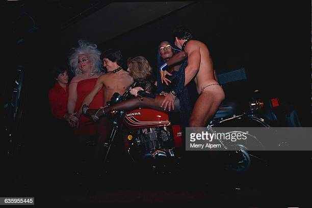 Grace Jones sits on a motorcycle with an exotic dancer while actors Jimmy Baio and Divine stand nearby with another exotic dancer and an unknown woman