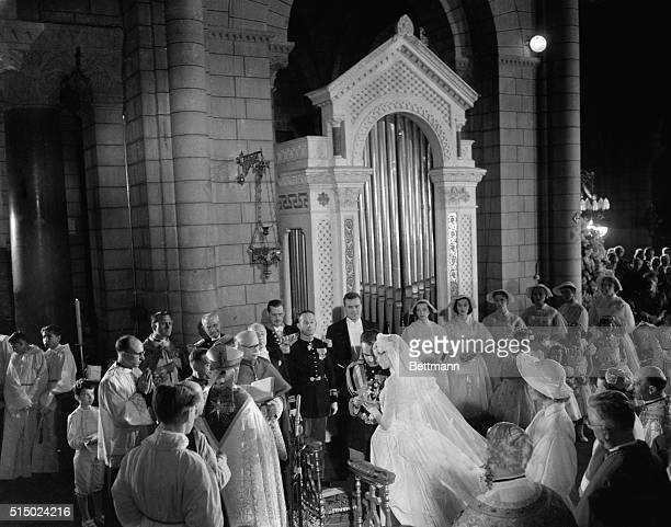 Grace Kelly and Prince Rainier as he has some difficulty putting the ring on his bride's finger during the religious ceremony in Monaco cathedral....