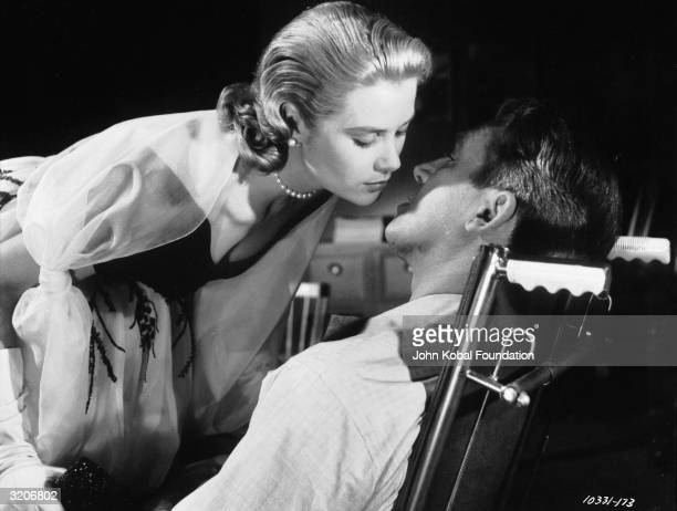 Grace Kelly leans over to kiss James Stewart in a scene from Hitchcock's suspense mystery 'Rear Window'