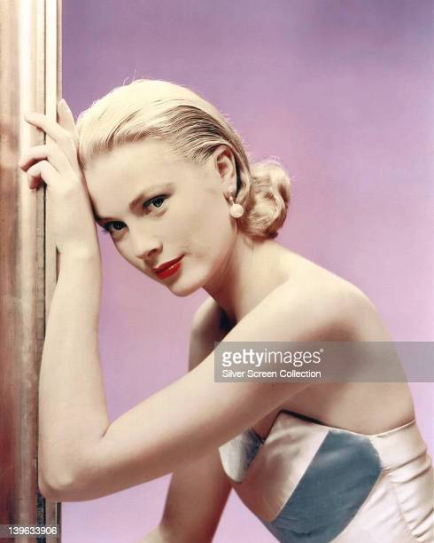 Grace Kelly US actress wearing an offtheshoulder dress in a studio portrait against a lilac background circa 1955