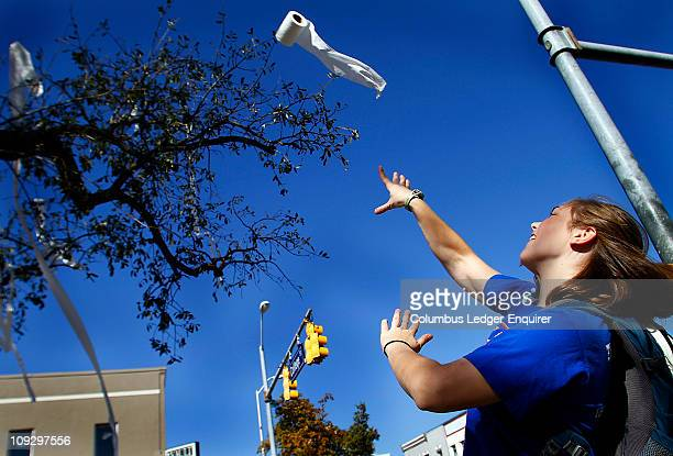 Grace Langhout an Auburn university freshman from Huntsville Alabama tosses a roll of toilet paper up into one of the two oak trees at Toomer's...