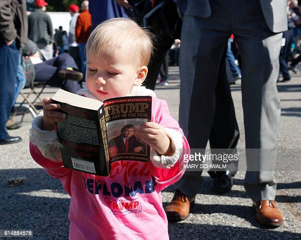 Grace Mahoney 16 months looks at a copy of The Art of the Deal before the start of an event with Republican presidential candidate Donald Trump on...