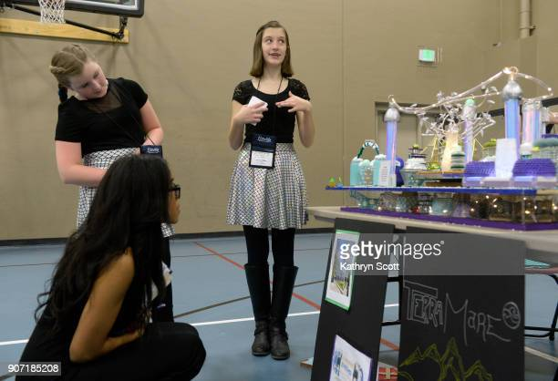 Grace Miller right and teammate Olivia Newitt standing left present their model city 'Terra Mare' to judges and visitors during the Future City...