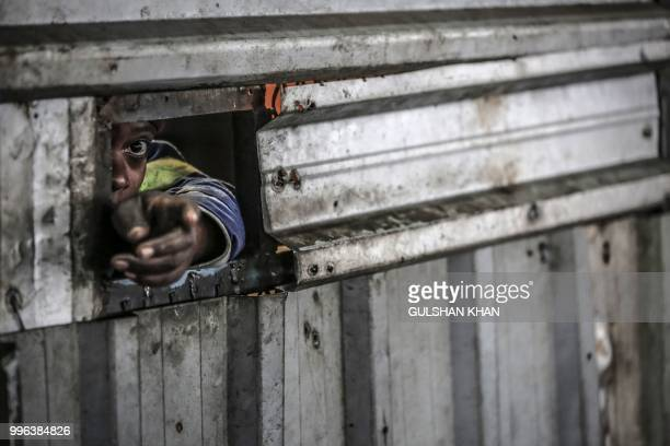 TOPSHOT Grace Mudimu calls a reclaimer to pay him through a metal door at Mudimu Recycling a buy back centre in Selby Johannesburg where reclaimers...