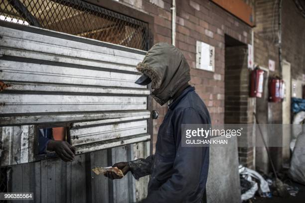 Grace Mudimu pays reclaimer through a metal door at Mudimu Recycling a buy back centre in Selby Johannesburg where reclaimers bring waste to be...