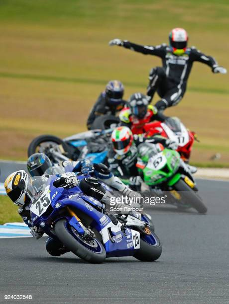 Grace Poutch of Victoria competes as Yannis Shaw of NSW crashes during race 2 of the Australian Supersport 300 Championship ahead of the 2018...