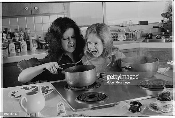 Grace Slick and her daughter China Kantner, make faces as they fix spaghetti at their stove.