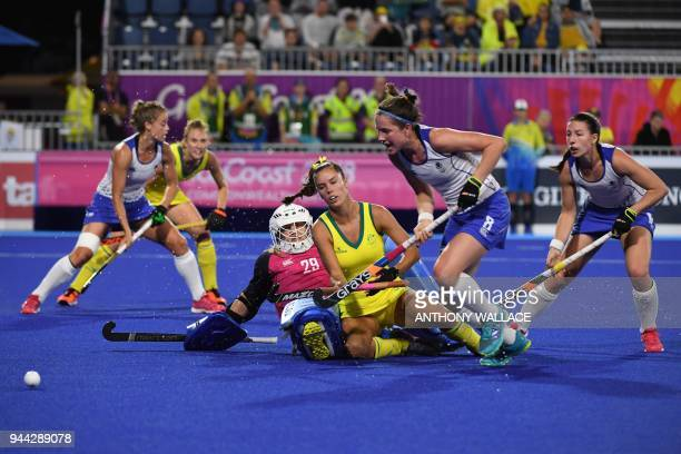 Grace Stewart of Australia falls next to Scotland's goalkeeper Amy Gibson as Amy Costello of Scotland chases the ball during the women's field hockey...
