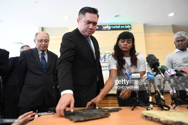 Grace Subathirai Nathan daughter of Malaysian Airlines flight MH370 passenger Anne Daisy hands over a piece of debris believed to be from flight...