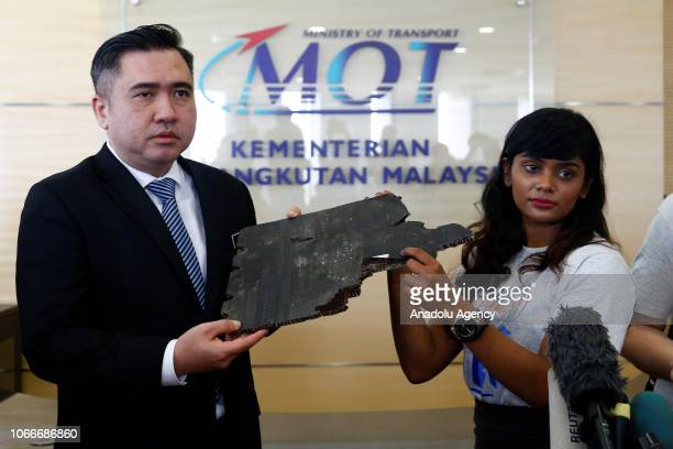 Grace Subathirai Nathan daughter of MH370 passenger Anne Daisy and Malaysia's Transport Minister Anthony Loke hold pieces of debris found in...
