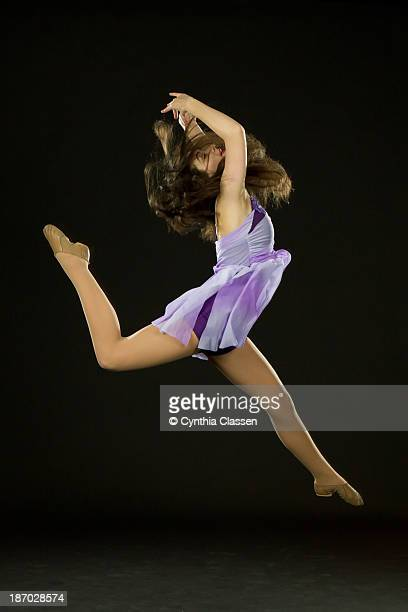 Graceful dancer doing a firebird leap