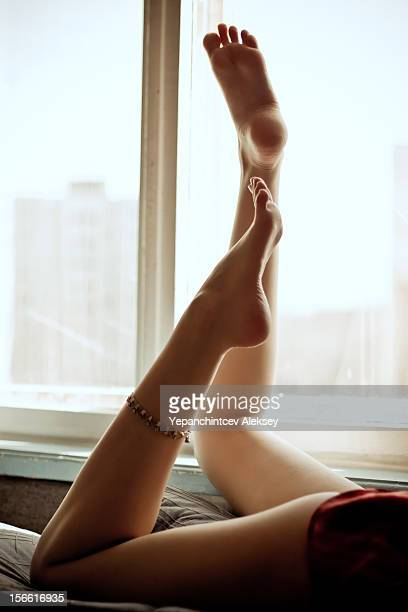 graceful girl feet - woman lying on stomach with feet up stock photos and pictures