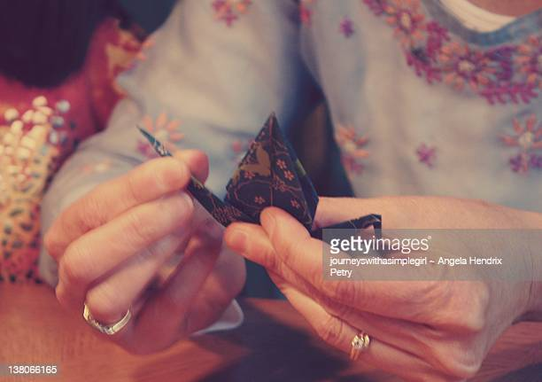 Graceful hands folding origami peace cranes