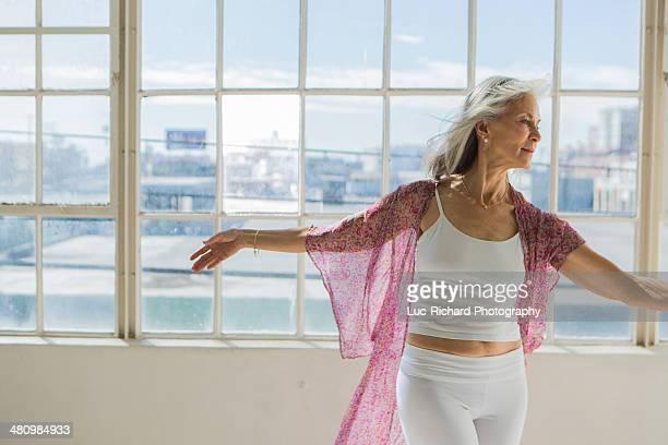 Graceful senior woman dancing in sunlit apartment