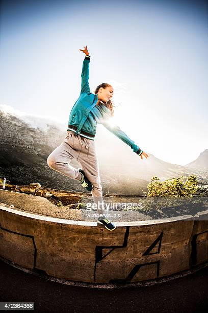 Graceful teen performing classical dance moves on a wall