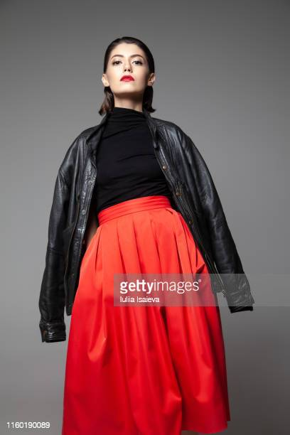 graceful young woman wearing black jacket in studio - leather skirt stock pictures, royalty-free photos & images