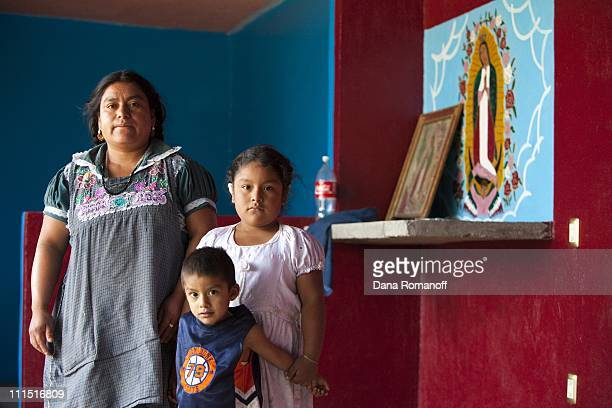 Gracia Cruz stands with her two children in her newly constructed home on November 21 2009 in the Zapotec town of San Marcos Tlapazola in the Central...