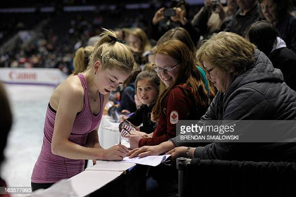 Gracie Gold of the US signs autographs after practicing at Budweiser Gardens in preparation for the 2013 World Figure Skating Championships in...