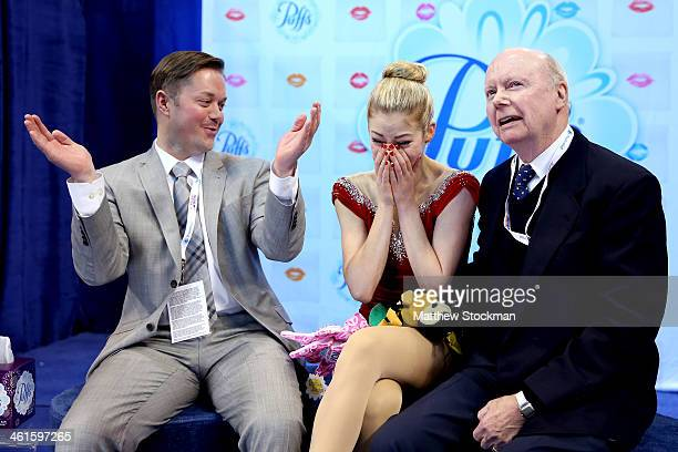 Gracie Gold reacts to her scores with coaches Scott Brown and Frank Carroll in the kiss and cry after skating in the short program during the...