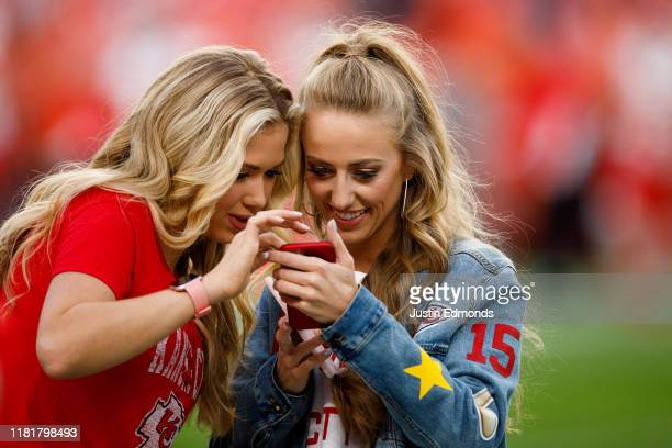 Gracie Hunt and Brittany Matthews, girlfriend of quarterback Patrick Mahomes of the Kansas City Chiefs check out social media on the field before a...