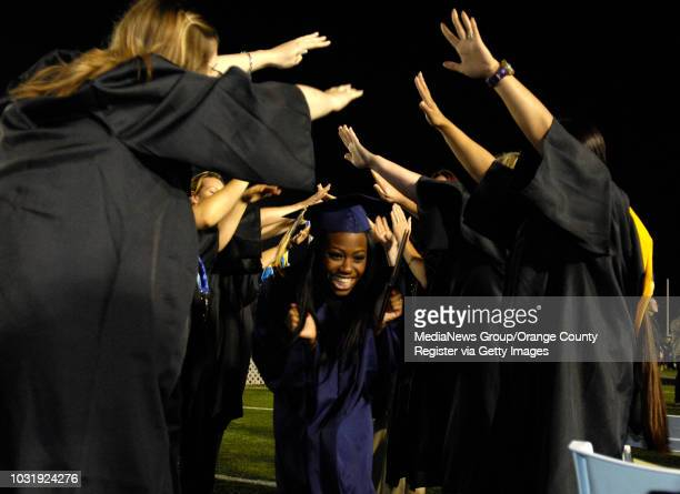 STADIUM Graduate Amber Miller runs through a tunnel of teachers after receiving her diploma during the commencement ceremony from Millikan High...