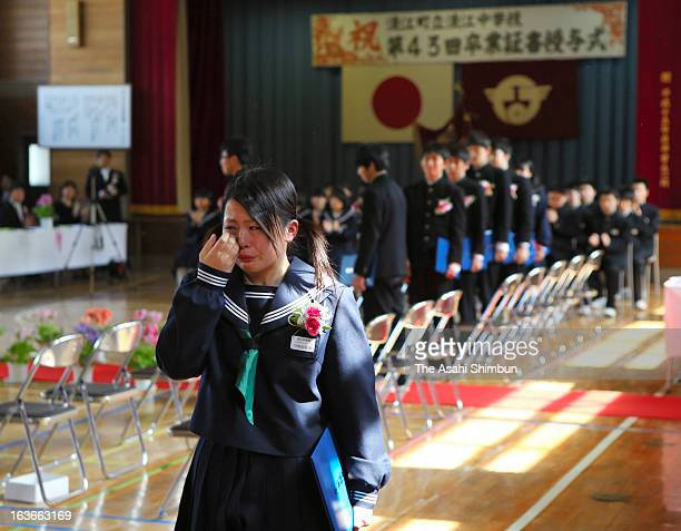 A graduate from Namie Junior High school originally located within the evacuation zone wipes her tears on the graduation day at the temporary school...