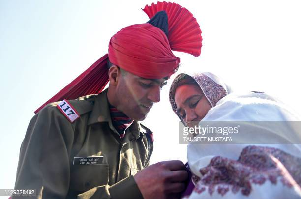 A graduate from the Jammu and Kashmir Light Infantry Regiment of the Indian Army shows his medal to his mother after a passing out parade after...
