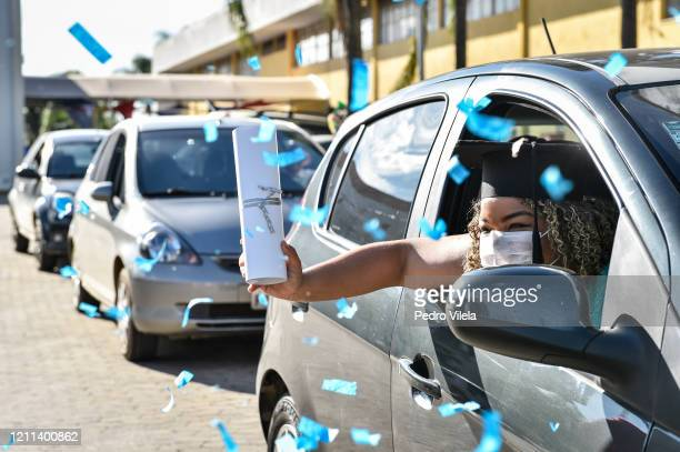A graduate from the medical and nursing school of Faseh University celebrates from a car after receiving the diploma during a drivethru ceremony to...