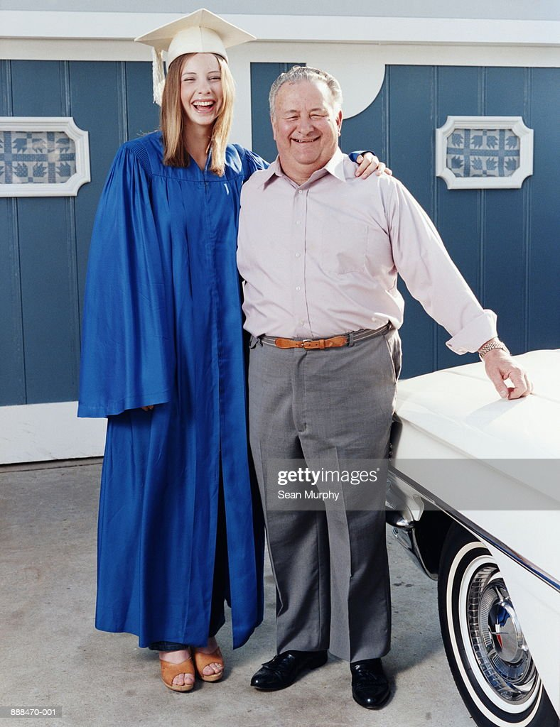 Graduate In Cap And Gown Standing With Father In Front Of Garage ...