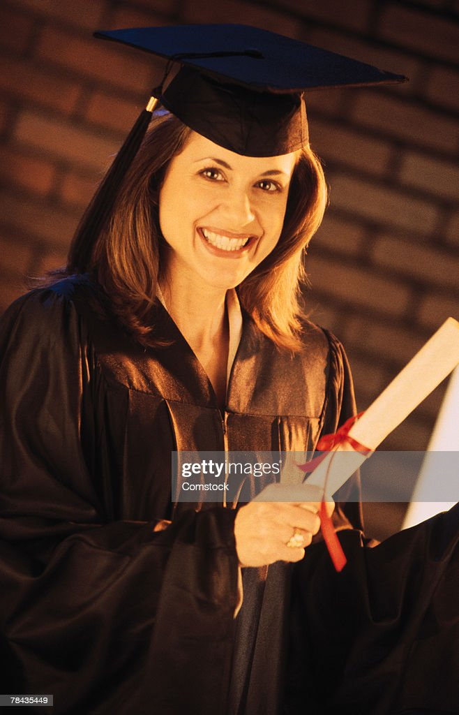 Graduate in cap and gown with diploma : Stockfoto