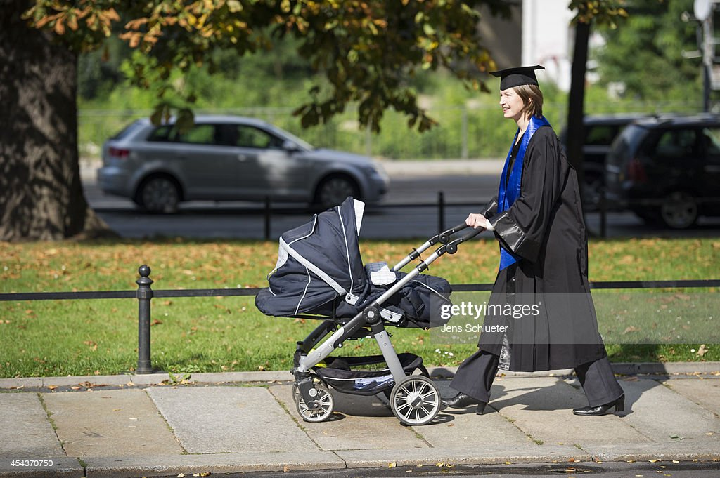 A Graduate in gown and caps push after their graduation at the HHL Leipzig Graduate School of Management a baby carriage on August 30, 2014 in Leipzig, Germany. A total of 167 students in various Masters programs of business management graduated today, including the regular MBA program, whose students are 80% from foreign countries, while the more advanced graduate programs have a higher percentage of German-born students.