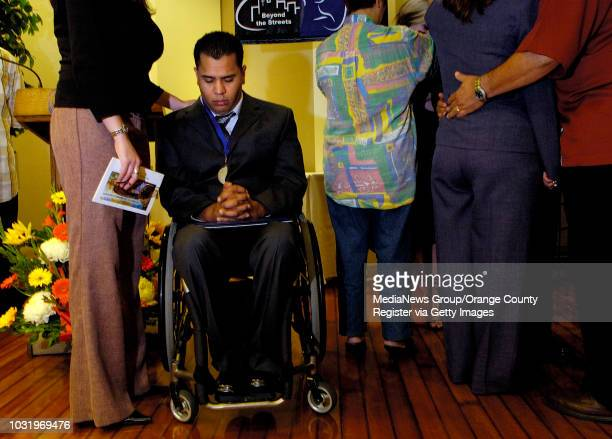 5/4/05 Graduate Lee Mercado in wheelchair stands with his fiancée Marlene Cardenas during a prayer at the end of the Beyond the Streets graduation...