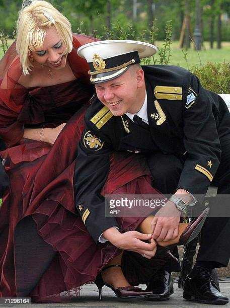 A graduate of a Naval school helps his friend strap her shoe during a reception for young officers outside St Petersburg 25 June 2006 AFP PHOTO/...