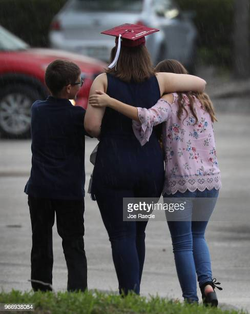 A graduate of Marjory Stoneman Douglas High School is hugged as she heads to her car after attending the graduation ceremony at the BBT Center on...
