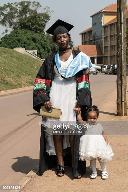 A graduate poses with her daughter before the 68th graduation ceremony where more than 14 000 students received degrees at Makerere University in...