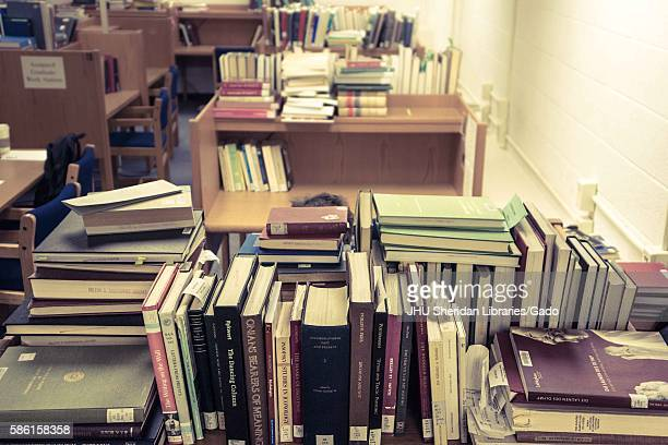 A graduate student sits at his work space surrounded by piles of books in the Milton S Eisenhower Library on the Homewood campus of the Johns Hopkins...
