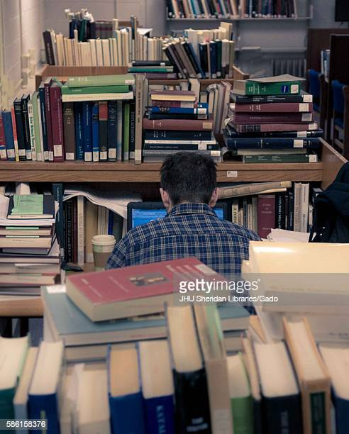 Graduate student sits at his work station on his laptop, surrounded by piles of books, in the Milton S. Eisenhower Library on the Homewood campus of...