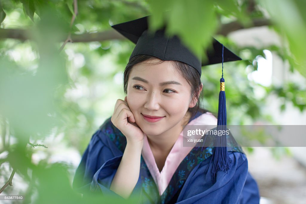 Graduate Student Wearing Graduation Gown And Holding Cap Under Tree ...