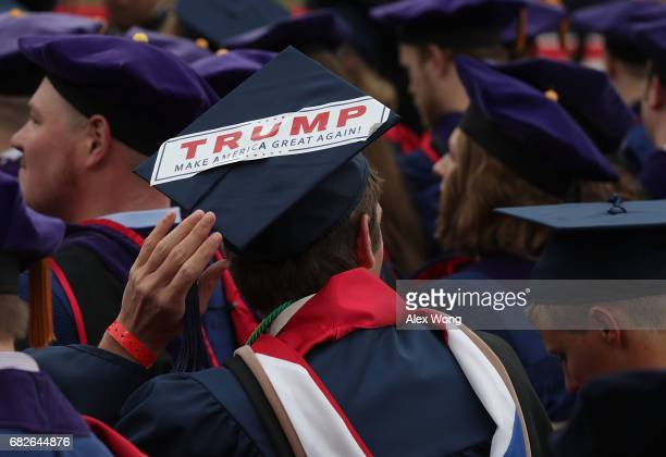 A graduate wears a cap decorated with a Trump campaign sticker during the commencement at Liberty University May 13 2017 in Lynchburg Virginia...