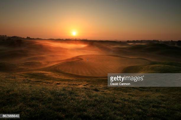 Graduated colour filter used on the camera in this image: The sun rises looking back down the 440 yards par 4, 12th hole on the Albatross Course at...
